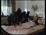 Alvó csajhoz három maszkos betörő mászik be és erőszakot tesznek a nőn, aki ezt láthatóan élvezi.