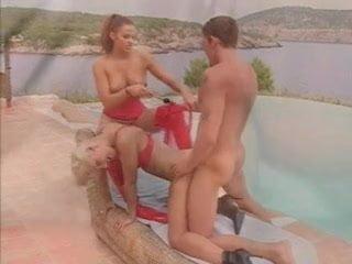 Nikki belucci piros ruhában játsza a szexrabszolgát és jól áll neki.
