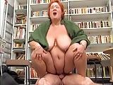 Vörös duci nő könyvtárban kefél