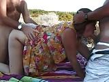 Érett nő érett faszokkal baszik a homokos tengerparton, szopja őket.